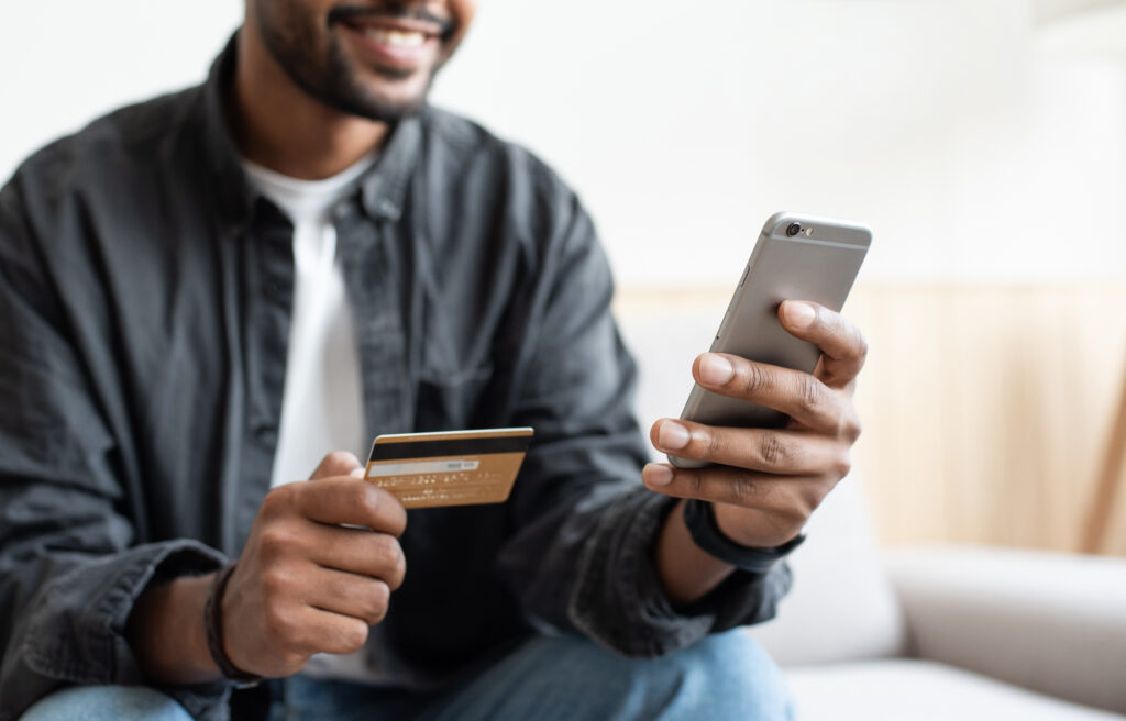 Person holding credit card and phone